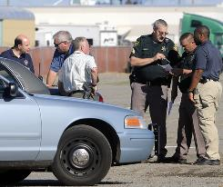 Officers from the Spokane County Sheriff's Department confer Thursday outside the Spokane County Fairgrounds. where a killer committed to a mental institution escaped.