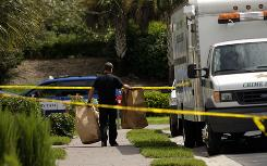 A Collier County Crime Scene Investigator removes bags of evidence from a home where authorities say Guerline Damas and her five children were found dead Saturday evening.