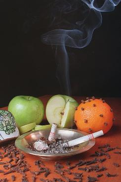 A clove cigarette burns in an ashtray surrounded by cloves, apples and an orange. Lawrence Deyton, director of the FDA's Center for Tobacco Products, says 17-year-old smokers are three times as likely to use flavored cigarettes as smokers over the age of 25.