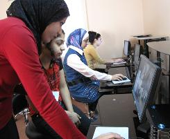 Zainab al-Hasani, 28, a teacher at Ishtar Internet Center in Baghdad, helps one of her students navigate the Internet.