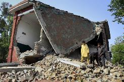 Local boys walks over the rubble  of the damaged portion of a girls school, wrecked by suspected militants in Pakistan on Tuesday.