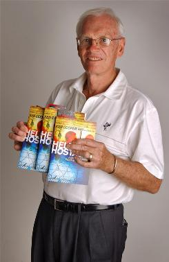 Ken Cooper holds copies of his book Held Hostage: A serial bank robber's Road to Redemption.