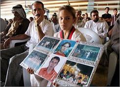 Maha Sa'ayd holds photos of her father and other members of the Iraqi National Taekwondo team at a meeting for the victims' families in Baghdad.