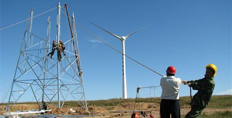 Workers install new power lines at the Dalian Tuoshan Wind Farm, the largest wind power farm in northeast China's Liaoning province.