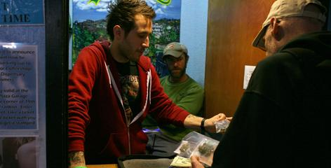 Jon Sarro, left, shows a customer different strains of medical marijuana at Coffeeshop Blue Sky in Oakland.