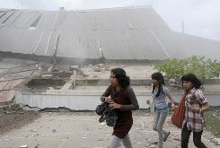 Students run near a collapsed university building after an earthquake hit Padang, on Indonesia's Sumatra island on Wednesday. 