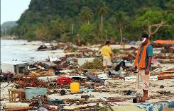 Men walk among the debris Wednesday on a beach in Lalomanu, Samoa. A tsunami devastated Samoa, American Samoa and Tonga on Tuesday after a morning earthquake.