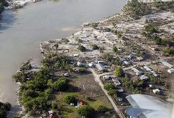 A powerful quake in the South Pacific hurled massive tsunami waves at the shores of Tonga, shown here, Samoa, and American Samoa flattening villages and sweeping cars and people back out to sea while leaving scores dead and dozens missing.