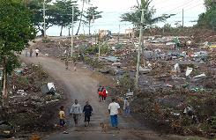 Samoans walk through a destroyed village outside Apia on Wednesday. Relief workers say the islands have been devastated and need everything for recovery.