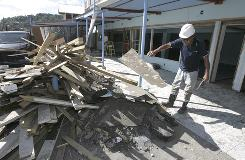 Paul Matgau'u helps clean up debris in one of the of the businesses on the waterfront of Pago Pago Bay on Saturday.