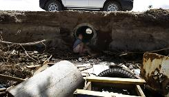 A child plays in a debris filled drain near the beach at Vailoa village, Samoa on Friday, three days after a deadly tsunami rolled through several South Pacific island nations.