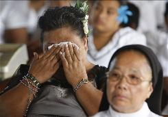 A woman wipes her face during a service Sunday at the Holy Cross Catholic Church in Leone, American Samoa, where a tsunami struck last week.