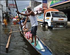 Residents travel the streets of Santa Cruz, Philippines, on Sunday. Tropical Storm Ketsana struck the Philippines on Sept. 26, killing about 300 people nationwide.