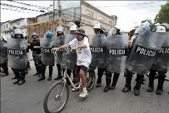 A supporter of Honduras' ousted President Manuel Zelaya sits on a bicycle near riot police during a demonstration in front of the U.S. embassy building in Tegucigalpa Oct. 5.