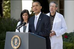 President Obama speaks in the White House Rose Garden as doctors Mona Mangat and Hershey Garner look on in Washington on Monday.