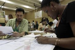"New York City resident Julio Jimunez, left, goes over a ""Point of Dispensing"" screening form with NYC Department of Health employee Crystal Green."