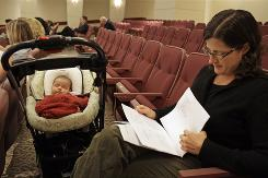 Angie Garling, right, of Berkeley, Calif., reads while attending a Proposition 65 developmental and reproductive toxicant identification committee hearing with her 7-week-old daughter Nina Garling-Rai in Oakland, in July. A state board voted that the proposition would not cover BPA.