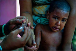 A child winces from a needle while a health service worker takes a blood sample for a malaria test in Dajabon, Domnican Republic, on the border with Ouanaminthe, Haiti, on Tuesday.