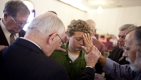 The Rev. Dennis Chisholm, left, and Jim Ellis lay hands on Colton Elbel, 13, at the Christian and Missionary Alliance Church. Chisholm says that despite the recession, his church hasn't experienced much of a downturn in giving.