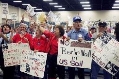 Protestors hold signs during a Dec. 11, 2007, protest rally against the building of a fence that will be placed along parts of the Rio Grande River, at the McAllen Convention Center in McAllen, Texas.