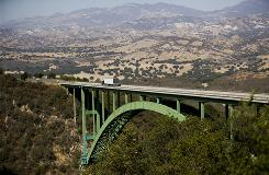 Traffic drives across Cold Spring Canyon Bridge in the hills behind Santa Barbara, Calif.