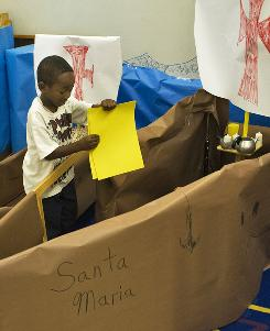 Kindergarten student Aaron Wilson loads supplies into a paper model of the ship Santa Maria during a lesson about the voyage of Christopher Columbus to the New World at Philip Shore School of the Arts in Tampa, Fla.