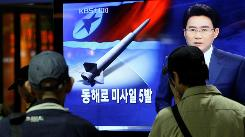 South Koreans at a train station in Seoul watch a TV report about North Korea's missile test.