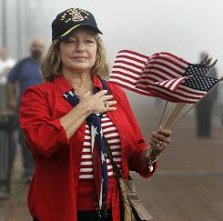 Geri Cavaretta of Madisonville, La., listens to the National Anthem before watching the USS New York sail down the Mississippi River in New Orleans on Tuesday. The ship was built with about eight tons of steel from the World Trade Center site and is on its way to New York, its home port.