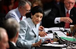 Sen. Olympia Snowe, R-Maine, looks toward colleagues before announcing she'll vote for the Finance panel's health care bill.