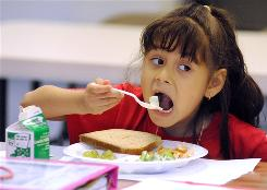 Odette Aguilar, 6, eats a lunch of baked chicken, celery, grapes and bread at the Latin American Community Center in Wilmington, Del.