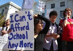 University of California-Berkeley students carry signs during a demonstration on campus in front of Sproul Hall protesting proposed fee hikes and service cuts at 10 University of California campuses. California's public university and community college systems educate about one in six American college students and is hardest hit during this recession.