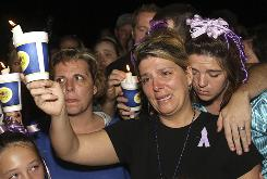 Diena Thompson, center, mother of Somer Thompson, shows her emotion at a candlelight vigil for her daughter on Thursday in Orange Park, Fla.