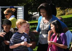 First lady Michelle Obama talks to children at a Healthy Kids Fair on Wednesday at the White House. She is viewed favorably by 61% in poll.