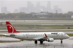 The Minneapolis skyline rises through the rain as an arriving Northwest Airlines jet taxis at Minneapolis-St. Paul International Airport on Friday. Investigators are looking into a Northwest flight bound for Minneapolis from San Diego that over flew the airport by 150 miles.