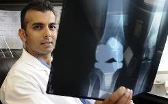 Orthopedic surgeon Yogesh Mittal, examining X-rays in Tulsa, says Medicare bonus payments have given him an incentive to keep costs down that he didn't have before.
