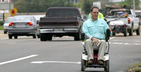 Disability-rights advocate Scott Crawford of Jackson, rides down Terry Road in Jackson, Miss. on Friday in his motorized wheelchair.