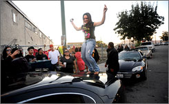 A woman dances atop a car while visiting a temporary memorial for three people killed during sideshow activity in Oakland, on Friday, Oct. 23, 2009. The woman, who gave her name as Madame Torres, said her cousin was Zsorhzinnia Tevaseu, 19, of San Lorenzo, a mother who was one of the three people killed in a 'sideshow' crash.