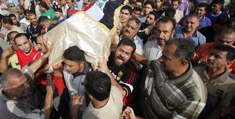 Mourners carry a coffin on Monday of a victim who was killed in a suicide bombing in Baghdad, Iraq.