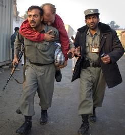 A German man with a broken foot is carried away from the scene of a suicide bomb attack on an international guest house in Kabul.