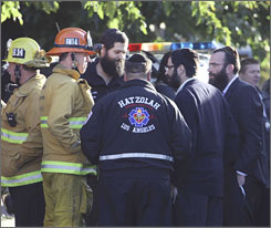 Los Angeles firefighters and synagogue parishioners huddle at the scene in Los Angeles where a gunman shot and wounded two men in the legs early Thursday.