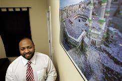 Sekou Jackson poses next to a picture of Mecca in his home Washington.