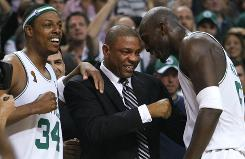 "Boston Celtics observers might see this gesture more often in the near future from coach Doc Rivers, seen here between Paul Pierce, left, and Kevin Garnett in June 2008. Rivers says he has become more of a ""fist bumper"" instead of a ""handshaker."""