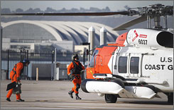 Coast Guard pilots prepare a MH-60 Jayhawk helicopter before taking off on a search mission at the San Diego Coast Guard Station on Friday.