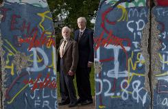 "Baxter Watson, left, and Bob Hawkins stand next to ""Breakthrough,"" a sculpture made from parts of the Berlin Wall by Edwina Sandys, granddaughter of Winston Churchill."