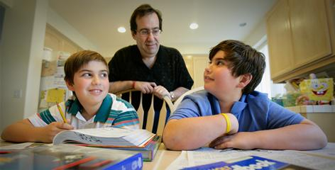 Jonathan Hirsch, 11, left, and brother Samuel, 9, of Lomita, Calif., study as their father, Howard, checks their progress. Howard Hirsch, who participated in the Stress in America survey, says his sons can see the financial worry on his face.