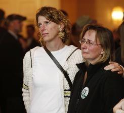 Gay marriage supporters Karen Weiss, left, comforts Jennifer Hoopes as they watch election results Tuesday at the Protect Maine Equality election night rally in Portland.