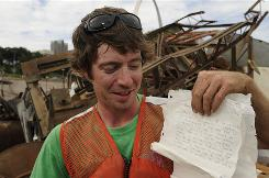 Chad Pregracke, owner of Living Lands and Waters, has found and collected dozens of bottles containing messages over the years during river cleanups. He holds just a sampling in St. Louis, Mo.