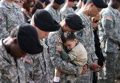 An unidentified soldier holds his son as the prayer Invocation is given during the memorial ceremony for victims of the Fort Hood shooting held Tuesday.