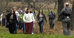 New York State troopers lead students and staff away from Stissing Mountain High School in Pine Plains, N.Y.