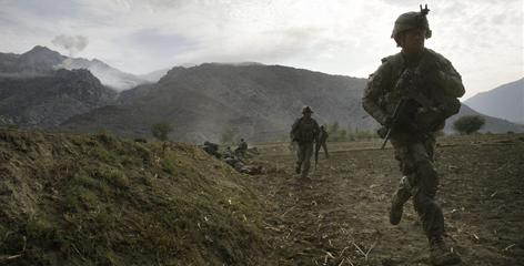 U.S. soldiers pull back from a farm field where they took cover from a Taliban attack Nov. 3 in Afghanistan. U.S. and Afghan officials agreed on a new nationwide plan to funnel aid to villages that help with security.
